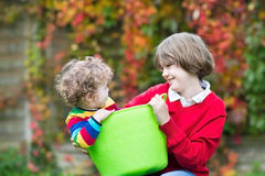 Laughing boy playing with his little baby sister in a laudry bas Stock Photos