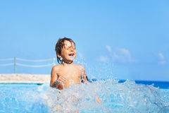 Laughing boy plays and splashes water around him Stock Photos