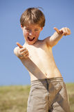 Laughing boy posing thumbs up Royalty Free Stock Photo