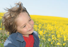 Laughing boy on a rapeseed field Stock Images