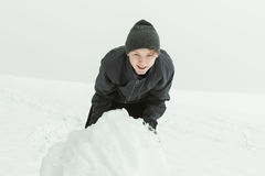 Laughing boy rolling a large snowball outside Royalty Free Stock Image