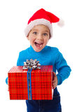 Laughing boy in Santa hat with red box Royalty Free Stock Images