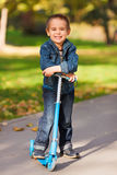 Laughing boy with scooter Stock Photos