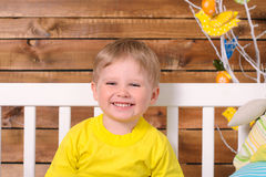 Laughing boy sitting on bench indoors Stock Image