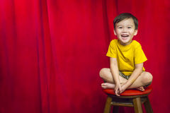 Laughing Boy Sitting on Stool in Front of Curtain Royalty Free Stock Photo