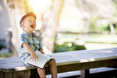 Laughing Boy Sitting on Table during Daytime Stock Image