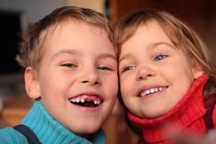 Laughing boy  and smiling girl. Laughing boy without foreteeth and smiling girl Royalty Free Stock Images
