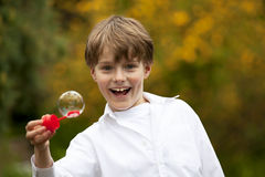 Laughing boy with a soap bubble. A handsome eight years old laughing boy having fun with a soap bubble Royalty Free Stock Photography