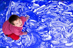 Laughing boy splashing hands in large painting stock photo