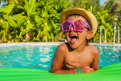 Laughing boy in star-shaped sunglasses on airbed Royalty Free Stock Image