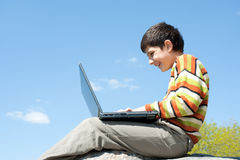 Laughing boy studies outside Stock Images