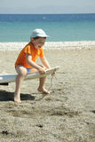 Laughing boy on wind surf. Boy in orange t-shirt sitting on windsurf and laughing Royalty Free Stock Images