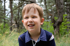 Laughing boy 4-5 years old. European laughing boy 4-5 years. Close-up on a background of grass and trees Stock Photos