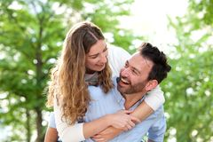 Laughing boyfriend carrying girlfriend outside in park Royalty Free Stock Photography
