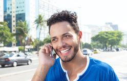 Laughing brazilian man at phone at city. With modern buildings and traffic in the background Stock Photo