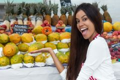 Laughing brazilian saleswoman at farmers market with tropical fr. Laughing brazilian saleswoman outdoors at latin american farmers market with tropical fruits stock photo