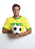 Laughing brazilian soccer fan with ball behind signboard Stock Image