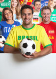 Laughing brazilian soccer fan with other fans behind signboard stock images
