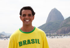 Laughing brazilian sports fan at Rio de Janeiro. With beach and Sugarloaf mountain in the background Royalty Free Stock Photography
