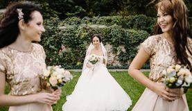 Bride with bridesmaids on the park on the wedding day. Laughing bride and bridesmaids tell funny stories standing on footsteps outside stock image