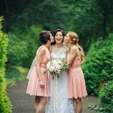 Laughing bride and bridesmaids tell funny stories standing in the park. Bridesmaids kiss beautiful bride standing outside in the park Royalty Free Stock Photography