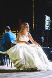 Laughing Bride on Chair. Laughing bride sitting on chair and groom behind her Royalty Free Stock Image