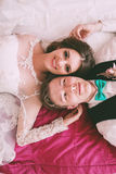 Laughing bride and groom lying on bed Royalty Free Stock Photos
