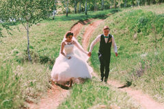 Laughing bride and groom running on road Stock Images