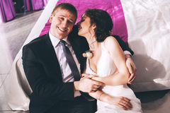 Laughing bride and groom sitting near bed Royalty Free Stock Photos