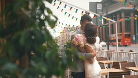 Newlyweds hugging on the summer terrace of the restaurant stock video