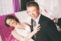 Laughing bride and groom in sunny bedroom Royalty Free Stock Photos