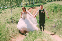 Laughing bride and groom walking on road. At sunny day Stock Photo