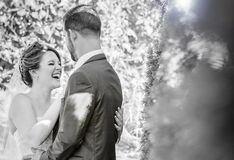 Laughing bride at ourdoor garden wedding. A bride laughing with her groom during an outdoor garden wedding in black and white Royalty Free Stock Photography