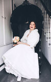 Laughing bride sitting in black chair. Happy laughing bride sitting in black chair Stock Images