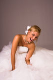 Laughing bride in white dress. Laughing young bride in white wedding dress, studio background Royalty Free Stock Photography
