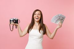 Laughing bride woman in wedding dress holding retro vintage photo camera, bundle lots of dollars, cash money choosing. Staff, photographer isolated on pink royalty free stock photo