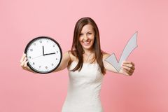 Laughing bride woman in wedding dress showing check mark and round alarm clock on camera on pink background. Time is running out. Wedding to do list stock photo