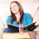 Laughing brunette with menu Royalty Free Stock Photography