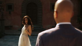 Laughing brunette reaches her hand out to bald-headed man stock video footage