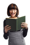Laughing brunette schoolgirl looking front. Hold book in her hands over white background Royalty Free Stock Images