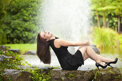 Laughing brunette woman sitting at pond Royalty Free Stock Images