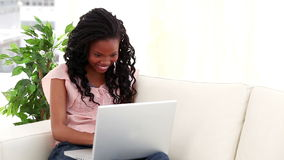 Laughing brunette woman using a laptop Stock Photo