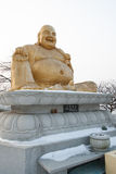 Laughing Buddha statue. Laughing Buddha gold statue in a temple with snow and white background stock image