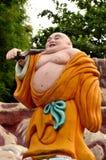 Laughing Buddhist monk on journey. A saffron robed fat laughing Buddhist monk carrying stick and satchel on his travels. Haw Par Villas park, Singapore Stock Photos