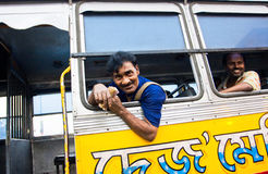 Laughing bus ticket seller looks out the bus window Royalty Free Stock Image
