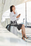 Laughing business woman with luggage and cellphone Royalty Free Stock Photos