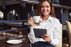 Laughing business woman reading latest news on tablet Royalty Free Stock Image