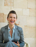 Laughing business woman sitting on chair Stock Images
