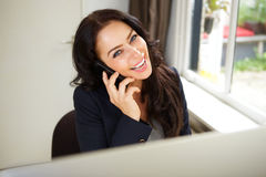 Laughing business woman sitting and talking on cellphone Stock Photos