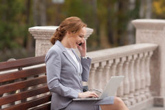 Laughing business women with laptop. Laughing business woman with laptop sitting on the bench Royalty Free Stock Photo